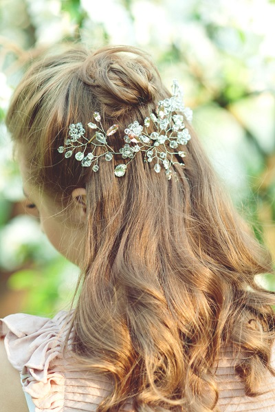 Closeup image of Girl with beautiful hairstyle decorated by shiny haircomb with  rhinestones, rear  view